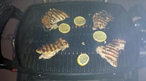 Chicken thighs and lemon slices on a smoky grill