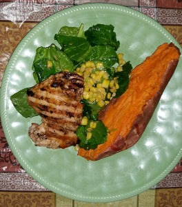 Grilled hot sauce-butter chicken with corn and spinach salad and baked yam