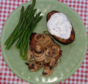 Steak under sauteed mushrooms and onions with roasted potato and steamed asparagus