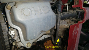 Side cover removed exposing carburetor