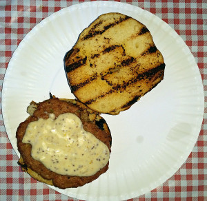Turkey burger with special sauce on pretzel roll