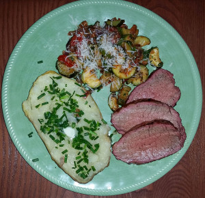 Tri-tip plated with baked potato and zucchini