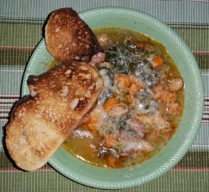 Sausage and white bean with spinach stew covered with fresh grated parmesan cheese