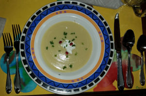 Cream of celery soup with a dollop of creme fraiche, chopped chives and pomegranate seeds